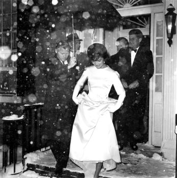 Jacqueline Kennedy lifts the skirt of her ivory double-faced silk satin twill inaugural ball gown, designed by Oleg Cassini, as she and her husband, President-elect John F. Kennedy, leave their Georgetown home in the snowfall en route to the inaugural concert in Washington, D.C., Jan. 19, 1961. (AP Photo/File)