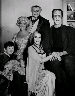 Publicity photo of the cast of the television program The Munsters. Seated, from left: Butch Patrick (Eddie), Yvonne DeCarlo (Lilly), Fred Gwynne (Herman). Standing: Beverly Owen (Marilyn) and Al Lewis (Grandpa).(Wikimedia Commons/CBS Television)