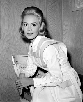 Actress Sandra Dee, portraying a nurse's helper in the motion picture production