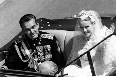 Princess Grace Kelly waves to cheering crowds lining the road as she rides in an open car with Prince Rainier III following their marriage in a religious wedding ceremony in the Monaco Cathedral, South of France, April 19, 1956. (AP Photo)