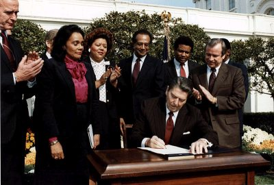 Coretta Scott King looks on as President Reagan signs the bill making Dr. King's birthday a national holiday, 1983. (Wikimedia Commons/White House Photo)