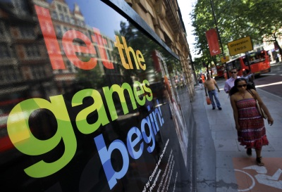 Pedestrians pass a poster advertising the 2012 Summer Olympics, Tuesday, July 24, 2012, in London. The city will host the 2012 London Olympics with opening ceremonies for the games scheduled for Friday, July 27. (AP Photo/Ben Curtis)