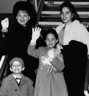 Judy Garland waves with her children, Liza, 15, top right, Lorna, 9, center, and Joe, 6, on Jan. 2, 1962, as they were about to board a TWA SuperJet at New York International Airport. Garland died on Jun. 22, 1969. (AP Photo / Paul Correri)