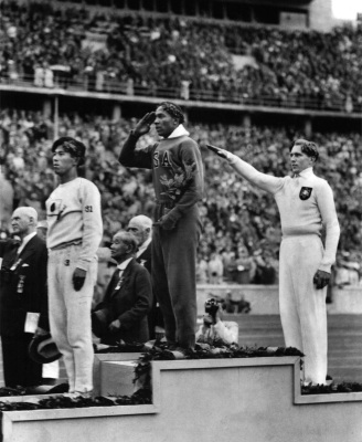 This Aug. 11, 1936 file photo shows America's Jesse Owens, center, salutes during the presentation of his gold medal for the long jump, after defeating Nazi Germany's Lutz Long, right, during the 1936 Summer Olympics in Berlin. Naoto Tajima of Japan, left, placed third. T (AP Photo/File)
