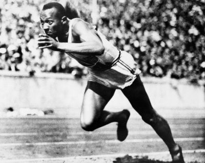 In this is Aug. 14, 1936 file photo, Jesse Owens competes in one of the heats of the 200-meter run at the 1936 Olympic Games in Berlin. The performance of Jesse Owens will be honored in the stadium where he won four gold medals at the 1936 Olympic Games when the world championships are held in Berlin. (AP Photo, File)