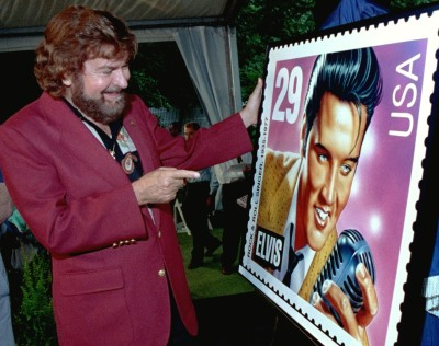 Sam Phillips, the owner of Sun Recording Studio where Elvis Presley cut his first record, smiles as he looks at a poster of the winning Elvis stamp design after the selection was announced Thursday morning, June 4, 1992 at Graceland, Elvis' home in Memphis, Tennessee. (AP Photo/John L. Focht)