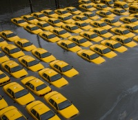 In this Oct. 30, 2012 file photo, a parking lot full of yellow cabs is flooded as a result of Superstorm Sandy in Hoboken, N.J. Sandy damaged or destroyed several homes and businesses, more than 72,000 in New Jersey alone, according to Gov. Chris Christie. (AP Photo/Charles Sykes, File)