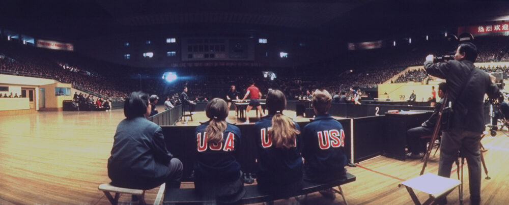 Members of the American ping pong team watch match in progress between a teammate and a Chinese opponent