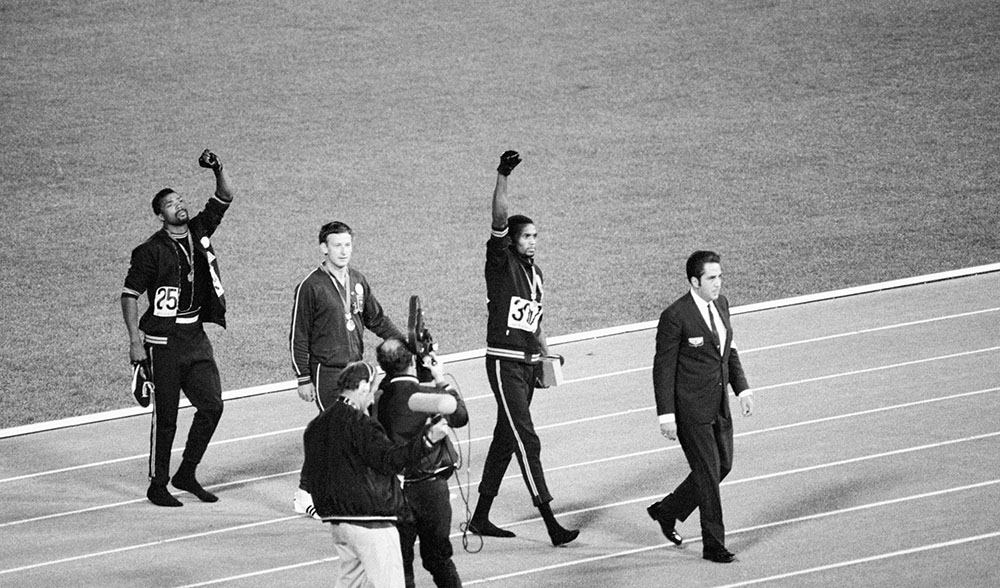 Carlos, Norman, and Smith leave the field in Mexico City after Black power salute