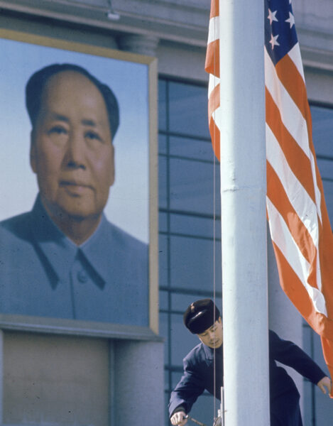 American flag is raised in China with Mao Zedong portrait in the background